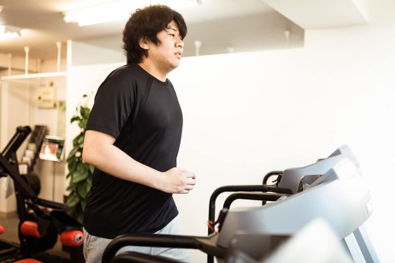 食べ物のことを考えながらダイエットに励む太った男性