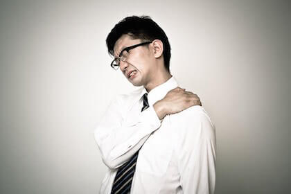 肩こりがひどくて湿布を貼ろうとしているビジネスマン