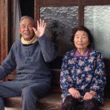 庭先で仲良く会話している老人夫婦